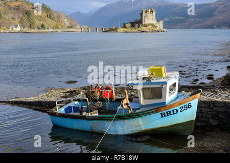 Fishing boat and Eilean Donan Castle at conjuction of Loch Duich, Loch Alsh and Loch Long near Dornie in Wester Ross, Highland Region, Scotland - Stock Image