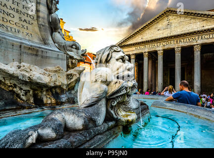 Closeup of the Fontana del Pantheon in the piazza della Rotonda as tourists sightsee with the ancient Pantheon in the background in Rome Italy - Stock Image