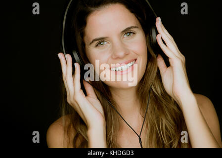 Young woman listening to headphones and smiling cheerfully, portrait - Stock Image