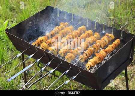 Shashliks from pieces of potatoes and bacon. Cooking of potatoes and bacon on fire. Picnic at nature. Barbecue lunch. Marinated shashlik from - Stock Image