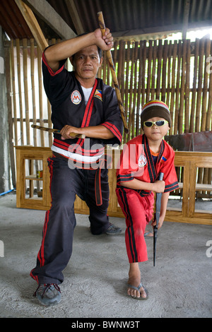An Arnis master stick fighter and his son strike a defensive posture in Mansalay, Oriental Mindoro, Philippines. - Stock Image