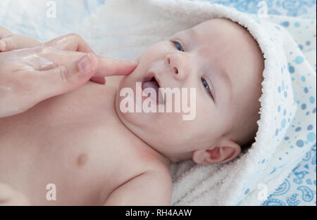 Applying cream over three months baby boy after bath. Bathing and skin sare for babies - Stock Image
