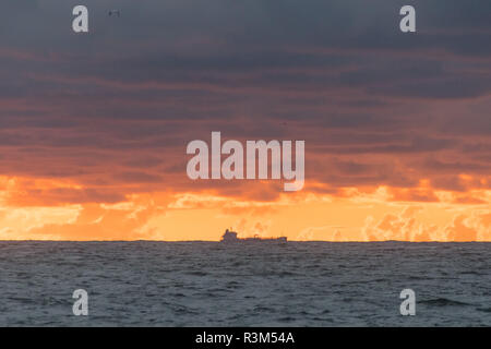 Mousehole, Cornwall, UK. 24th November 2018. UK Weather. After torrential showers yesterday, Mousehole was still looking cloudy at sunrise thie morning, with just a faint glimmer of colour on the horizon. Credit: Simon Maycock/Alamy Live News - Stock Image