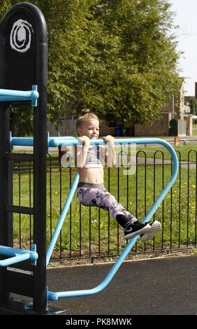 A six year old girl doing 'pull ups' on free to use equipment in an outdoor fitness area - Stock Image