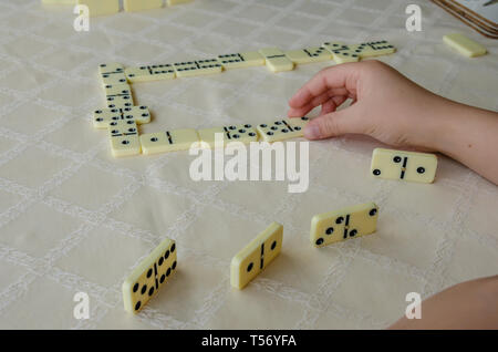 Close up view of a child's hand laying down a domino in a game of dominoes. - Stock Image