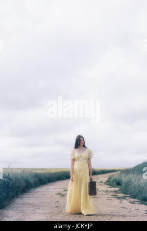 a young girl with a yellow dress is carrying a suitcase and is standing on a path through grainfields - Stock Image
