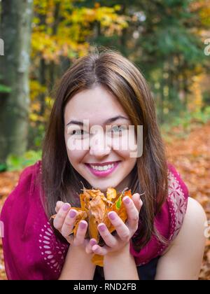 Pretty mesmerizing teen girl portrait is smiling at camera giggle giggling spontaneous joy - Stock Image