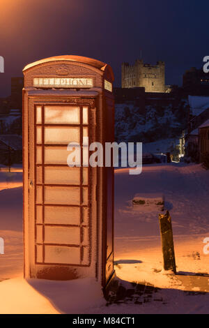 Traditional red phone box and Bamburgh Castle in winter snow, Northumberland, England. Winter (Feburary) 2018. - Stock Image