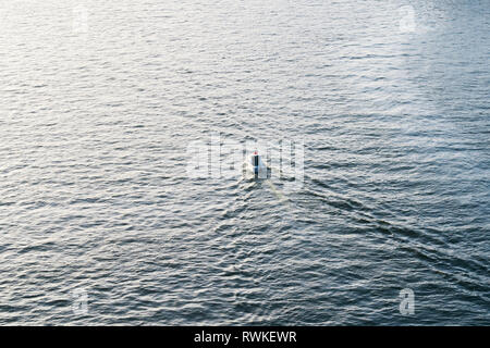 High angle view on single motorboat in the distance surrounded by blue ocean water in Porto, Portugal - Stock Image