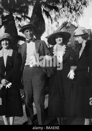 A group of adult stand together outside their house in California, ca. 1920. - Stock Image