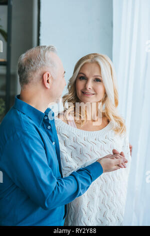 man looking at smiling wife while holding hands at home - Stock Image