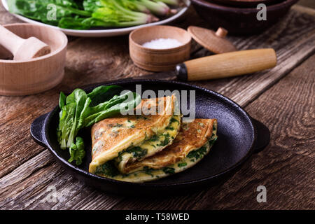 Spinach omelette in cast iron skillet, healthy vegetarian breakfast or brunch on wooden rustic table, close up, selective focus - Stock Image