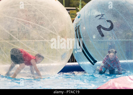 Anchorage, Alaska. 4th July, 2018. Children play inside giant plastic bubbles in Delaney Park during the annual Independence Day celebration July 4, 2018 in Anchorage, Alaska. Credit: Planetpix/Alamy Live News - Stock Image