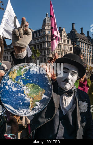 London, UK. 31st October 2018. Charlie X tells people to save Planet Earth at the Extinction Rebellion protest in Parliament Square hears speeches from climate activists including  Swedish schoolgirl Greta Thunberg, campaigner Donnachadh McCarthy, Labour MP Clive Lewis and economist and Green MEP Molly Scott Cato before making a 'Declaration of Rebellion' against the British Government for its criminal inaction in the face of climate change catastrophe and ecological collapse. Credit: Peter Marshall/Alamy Live News - Stock Image