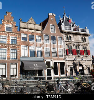 Facades, including the Teylers Museum, in Haarlem, the Netherlands. Bicycles are parked outside of the buildings. - Stock Image