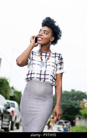 Beautiful African woman phoning in the street with a beautiful smile. - Stock Image