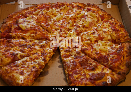 pepperoni and ham and pineapple pizza in box - Stock Image