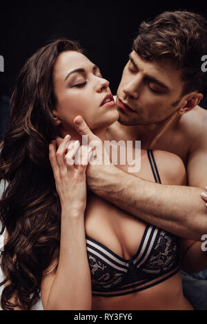 handsome man passionately touching neck of beautiful woman isolated on black - Stock Image