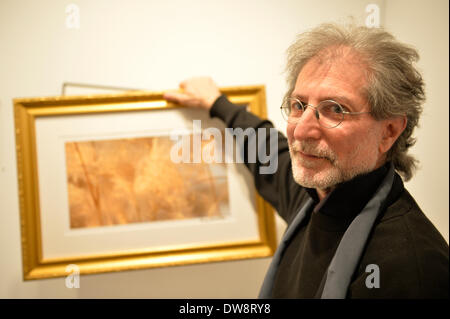 Huntington, New York, U.S. - March 1, 2014 -  Artist BARRY FEUERSTEIN holds one of his golden framed images at the Opening Reception '3 Wild & Crazy Artists' at FotoFoto Gallery, where he exhibited 'Red & White Paintings & Photographs – El Vocio Existential.' - Stock Image