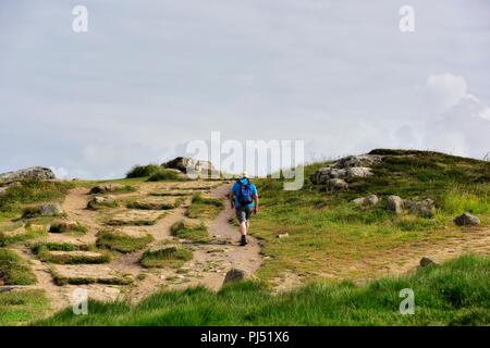 A lone man walking the south west coast path,Lands End,Cornwall,England,UK - Stock Image