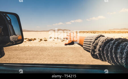 Girl close up hand playing with the wind like a wing outside the car traveling for alterntive vacation with desert and mountains outdoors view - holid - Stock Image