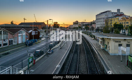 Lisbon, Portugal - Dec 30, 2018: High perspective view of railway track at Santos Station with 24 April Bridge in background at sunset - Stock Image