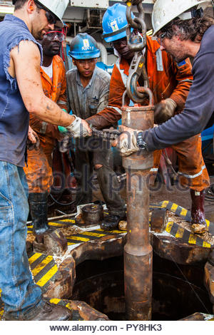 Workers with rusty pipe on offshore oil platform - Stock Image