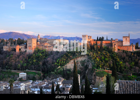 The Alhambra at dusk with the Sierra Nevada mountains in the distance. - Stock Image