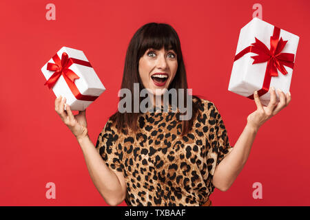 Image of a beautiful happy young woman dressed in animal printed shirt posing isolated over red background holding present box. - Stock Image