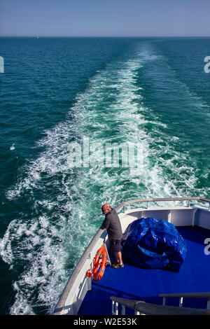 A passenger looking out to sea from the rear of a channel ferry from Brittany, France - Stock Image