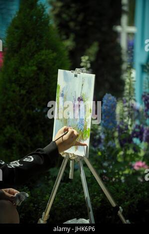 Artist painting flower scene on canvas - Stock Image