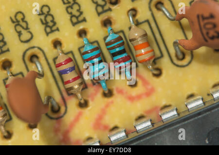 Macro-photo of resistors (carbon, and metal film [blue]), and capacitors on a printed circuit board (PCB). - Stock Image