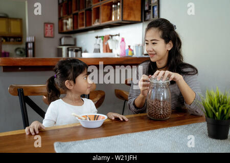 portrait of Little asian girl eating cereal for breakfast with mom - Stock Image