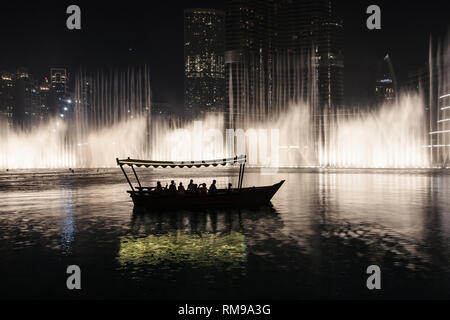 Tourists watching the Dubai Fountain show from a traditional boat, Dubai, United Arab Emirates. - Stock Image