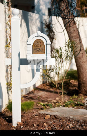 Bodrum, Turkey - January, 2019: White wooden US mail mailbox with metal emboss eagle symbol on the front yard of a house. - Stock Image
