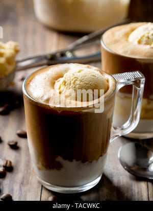 Iced coffe with vanilla ice cream called affogato in Italy on a rustic wooden table - Stock Image