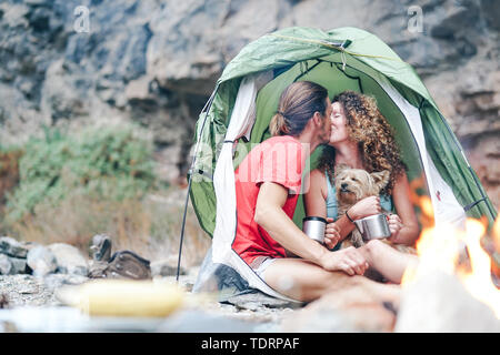 Travel couple camping in rock mountains after a trekking day - Happy people drinking hot tea inside tent with their dog next to bonfire - Stock Image