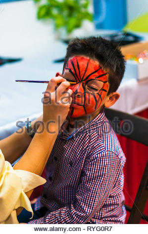 Poznan, Poland - March 3, 2019: Young boy with red and black paint on his face being painted with a brush by a woman during a birthday celebration par - Stock Image