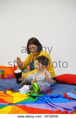 Woman and boy participating in drum lesson during a music class in Poznan, Poland - Stock Image