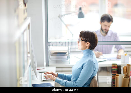 Side view of contemporary young manager or designer sitting by desk in front of computer screen and typing on keypad - Stock Image