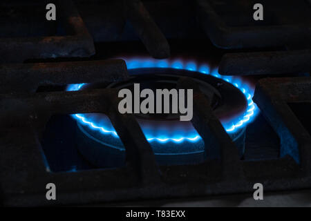 Stove with blue flame. Illustration of gas consumption. Crisis and rate hike in Argentina - Stock Image