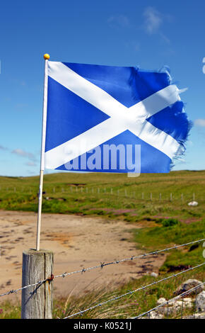 Saltire flag weathered by the fierce west coast winds on the Isle of Coll - Stock Image