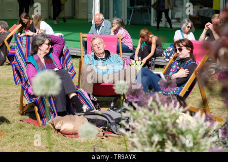 Hay Festival, Hay on Wye, Powys, Wales, UK - Friday 31st May 2019 - Visitors enjoy a break between events on the Festival lawns outside the bookshop as the sun emerges on Friday afternoon. The eleven day Festival features over 800 events many aimed at children - the Hay Festival continues to Sunday 2nd June. Photo Steven May / Alamy Live News - Stock Image