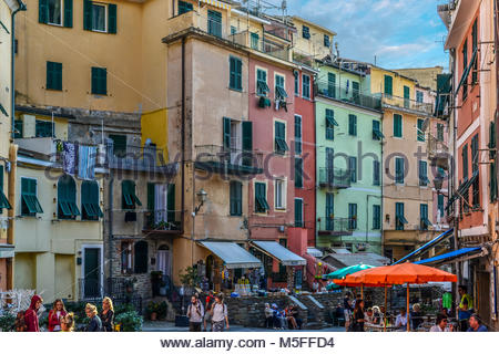 Tourists and locals mix in a small piazza at the colorful fishing village of Vernazza, Cinque Terre Italy - Stock Image