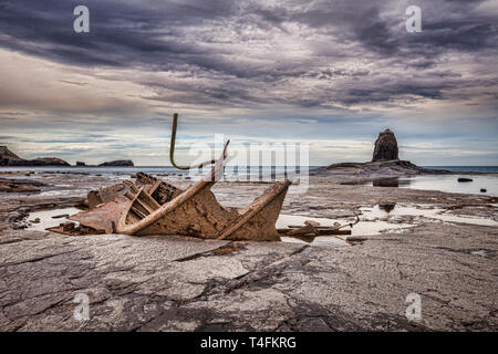 The wreck of the trawler 'Admiral van Tromp' on the shore at Saltwick Bay, near Whitby, North Yorkshire, with Black Nab in the background. - Stock Image