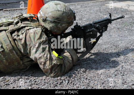 Sgt. Stephen Chawporn, assigned to 18th Military Police Brigade, runs through a stress shoot after performing physical tasks during the 2018 21st Theater Sustainment Command Best Medic Competition August 28, 2018 at Baumholder, Germany.During the second day of the competition competitors encountered a CBRN event, stress shoot, mystery event, and daily non-combat related tasks.#21BMC2018 #FirstInSupport #StrongEurope #18thMPBDE(U.S. Army photo by Sgt. Benjamin Northcutt 21st Theater Sustainment Command) - Stock Image