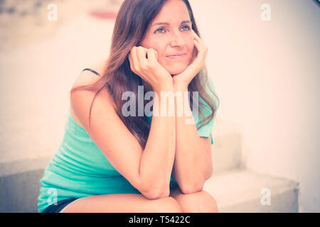 Thoughtful beautiful young woman with black long hair smile kindly whie sit down on a staris - people outdoor in his own thougths - cute caucasian fem - Stock Image