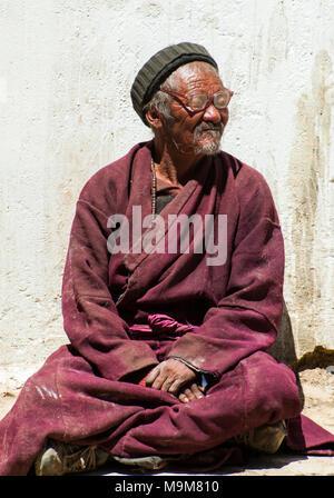 Elderly spectator at a Buddhist monastery festival at Korzok, a remote hamlet beside (Lake) Tso Moriri in Ladakh, India - Stock Image