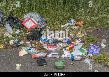 Domestic rubbish dumped / fly tipped in a car parking area. Personal environmental pollution at its worst. Contains 'brand' names so RM editorial only - Stock Image