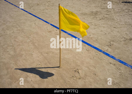 Yellow flag and the blue line on the golden sand beach - Stock Image